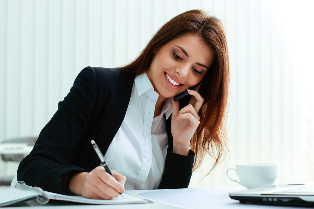 Young happy businesswoman talking on the phone and writing notes in office.jpeg